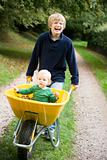 Boy pushing toddler in wheelbarrow