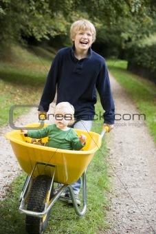 Boy pushing toddler in wheelbarrow