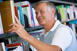 Senior man pulling a library book off shelf