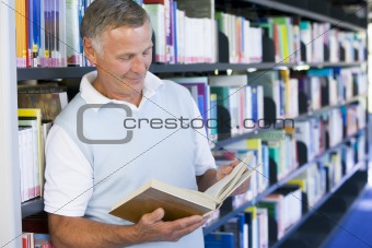 Senior man reading in a library