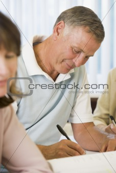 Senior man studying with other adult students