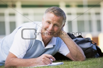 A man writing notes while lying on a campus lawn