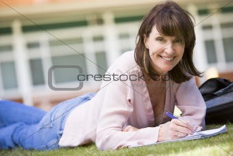 A woman writing notes while lying on a campus lawn