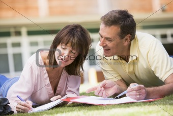 A man and woman writing notes while lying on a campus lawn