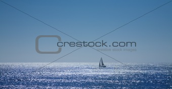 calm ocean and sailing boat in the distance