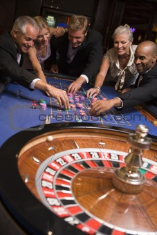 Group of friends gambling in casino