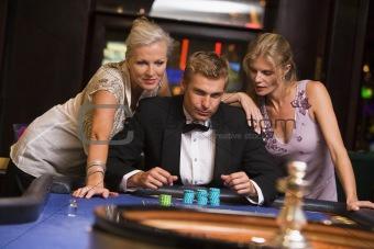 Man with glamorous women in casino