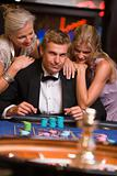 Man gambling in casino surrounded by attractive women