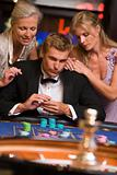 Man gambling at casino surrounded by glamorous women