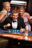 Man winning at roulette table surrounded by glamorous women
