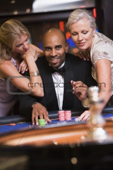Man in casino with glamorous women