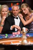 Man at roulette table with beautiful women