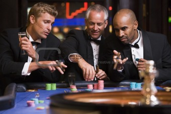 Group of men gambling at roulette table
