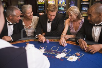 Group of friends playing blackjack in casino