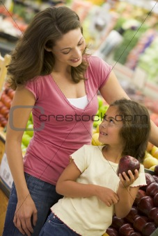 Mother and daughter shopping in produce section