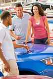 Couple discussing new car with salesman