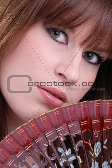 Cute young lady hiding behind fan