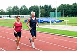 Senior Couple Running On A Track