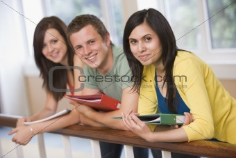 Three college students leaning on banister