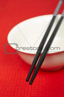 Pair of chopsticks and white bowl