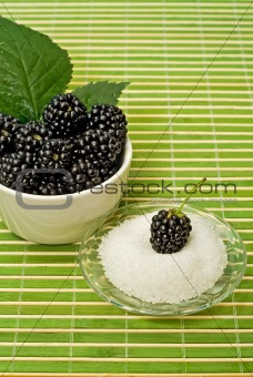 Blackberries in a bowl and sugar