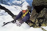 Mountaineer using an ice axe to climb a steep slope
