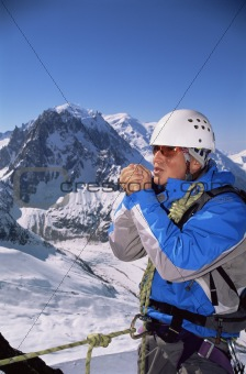 Young man warming hands on mountain peak