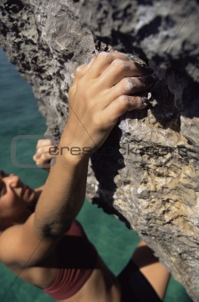A young woman climbing up a rock face