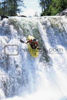 Young man kayaking down waterfall