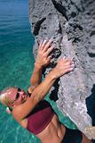 A young woman climbing up a rock face