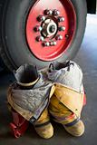 Empty firefighter&#39;s boots and uniform next to fire engine