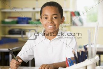 A schoolboy studying in class