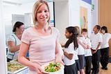 Teacher holding plate of lunch in school cafeteria