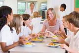 Teacher and schoolchildren enjoying their lunch in a school cafe