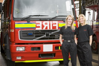 Portrait of two female firefighters standing by a fire engine