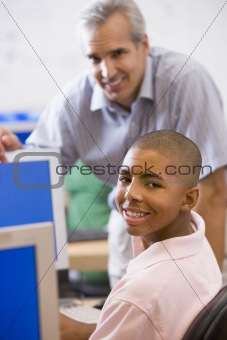 A teacher talks to a schoolboy using a computer in a high school