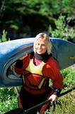 Young woman carrying kayak