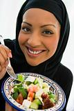 A Middle Eastern woman with a plate of salad