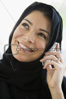 A middle eastern woman talking on a cellphone