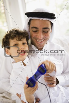 A Middle Eastern father and son playing a video game together