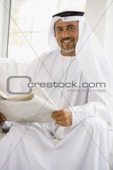 A Middle Eastern man reading a newspaper
