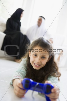 A Middle Eastern girl playing a video game