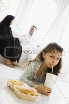 A Middle Eastern girl enjoying a fast food burger meal