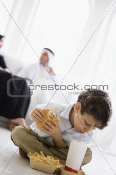 A Middle Eastern boy enjoying a fast food burger meal
