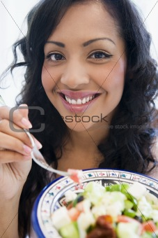 A South American holding a salad up to the camera