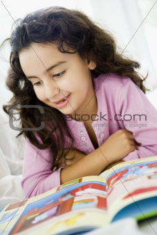 A Middle Eastern girl reading a book