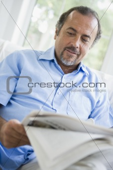 A Middle Eastern man reading a newspaper at home