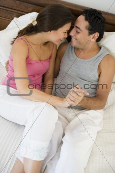 A Middle Eastern couple lying on a bed