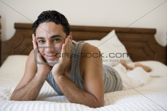 A Middle Eastern man lying on a bed