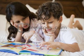 A Middle Eastern brother and sister reading together